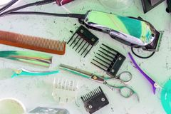 A Hair clipper and scissors with comb on white table. A Hair clipper and scissors with comb Barber on white mess up table from hair royalty free stock images