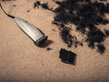 Hair clippers surrounded by hair Stock Photo