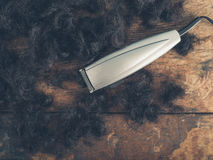 Hair clippers on wooden table. Hair clippers on a wooden surface surrounded by piles of cut hair Royalty Free Stock Image