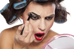 Hair curlers and bad make up. Crazy woman with curlers and bad makeup on white background royalty free stock photos