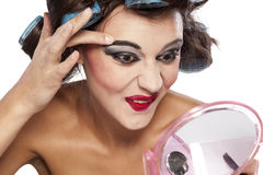 Hair curlers and bad make up. Crazy woman with curlers and bad makeup on white background stock image