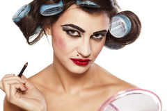 Hair curlers and bad make up. Funny woman with curlers and bad makeup on white background stock photo