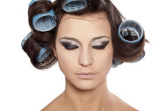 Hair curlers and bad make up. Funny woman with curlers and uncompleted bad makeup on white background Royalty Free Stock Photos
