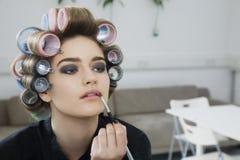 In Hair Curlers modelo que aplica o brilho do bordo foto de stock royalty free