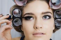 In Hair Curlers modelo que aplica o rímel fotos de stock