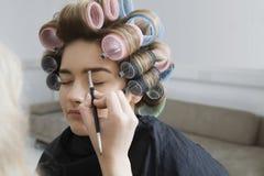In Hair Curlers modelo que hace maquillaje aplicar Fotografía de archivo