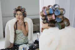 In Hair Curlers modelo que olha a reflexão fotografia de stock royalty free
