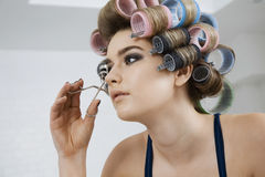In Hair Curlers modelo que usa o encrespador da pestana imagem de stock royalty free