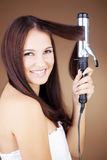 Hair curling. Portrait of young beautiful girl doing hairstyle Stock Images