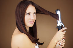 Hair curling. Portrait of young beautiful girl doing hairstyle Royalty Free Stock Photos