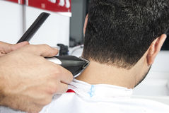 Hair cut. Barber cutting hair with electric razor at a barber shop Stock Photos