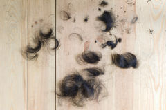 hair cut off on the wooden floor. Royalty Free Stock Photo