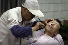 Hair cut on the streets. Various kinds of barbershops can be seen in cities of northeast China but some old men still prefer having their hair cut and face Royalty Free Stock Photo
