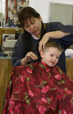 Hair cut wearing colorful barber's cape. Female hair salon owner cutting little boy's hair wearing colorful barber's cape Stock Photo