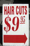 Hair Cuts Sign. A sign on a sidewalk, advertising hair cuts Royalty Free Stock Image