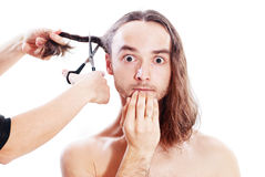 Hair cutting. Young frightened man with long hair in barbershop Stock Images