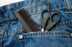 Hair cutting scissors and comb in jeans pocket Royalty Free Stock Photos