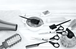 Hair cutting shears, combs, hair dye and professional cosmetics. For hair located on a wooden table Royalty Free Stock Photos