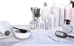Hair cutting shears, combs, hair dye and professional cosmetics. For hair located on white table Stock Photos