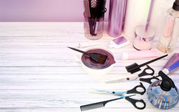 Hair cutting shears, combs, hair dye and professional cosmetics. For hair located on a wooden table Stock Images