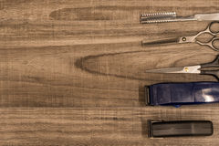 Hair Cutting Tools on a Wood Background. Various scissors, clippers, and razors for cutting hair royalty free stock photos