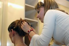 Hair dresser. A daughter working on mother's hair at a school exam Stock Photo