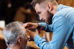 Hair dresser cutting bang of senior man Stock Photo