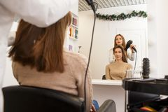 Hair dresser making style for a female client. Beauty salon`s life Stock Photos