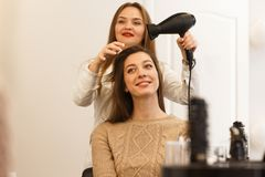 Hair dresser making style for a female client Royalty Free Stock Images