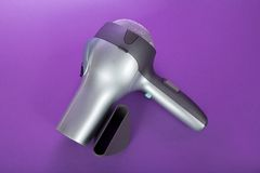 Hair dryer. The hair dryer for drying of hair and additional accessories, on the violet stock image