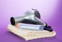 Hair dryer on fluffy towel shampoo and hairbrush Stock Photo
