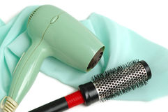 Hair dryer and hairbrush. The hair dryer and hairbrush on a satin background stock photography