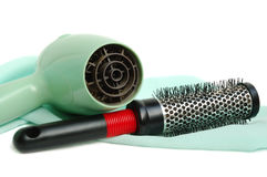 Hair dryer and hairbrush. The hair dryer and hairbrush on a satin background royalty free stock photos