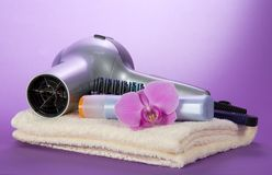The hair dryer, hairbrush, shampoo on a towel Royalty Free Stock Photography
