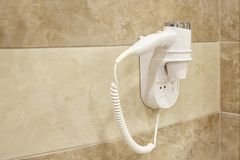 Hair dryer hanging on wall in bathroom of a hotel stock photos