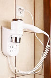Hair dryer. On the wall in bathroom stock image