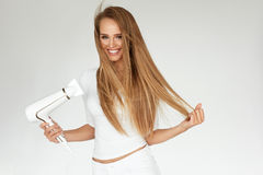 Hair Dryer. Woman Drying Beautiful Blonde Long Straight Hair Royalty Free Stock Images