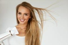 Hair Dryer. Woman Drying Beautiful Blonde Long Straight Hair. Hair Dryer. Beautiful Smiling Woman Drying Healthy Long Straight Hair Using Hairdryer. Portrait royalty free stock photo