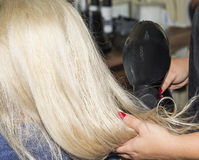 Hair drying with a blower. Detail of drying hair with hair dryer at the hairdresser Royalty Free Stock Images