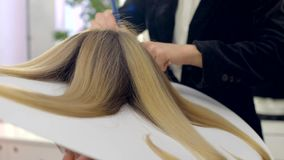 Hair dyeing. Hairdresser makes hairstyle, dye on special disk at a beauty salon. Hair covered in dye. view from above stock video footage