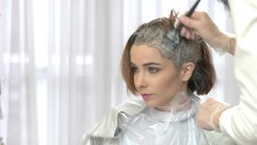 Hair dyeing process. Young woman in beauty salon. Hair dying tips stock video footage