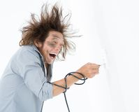 Hair on end. Man with hair standing on end plugging bared wire into a wall socket royalty free stock photography