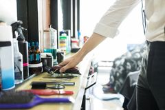 Hair Expert Keeping Trimmer On Counter In Salon royalty free stock photography