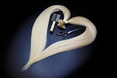 Hair extension equipment of natural blonde hair. heart shape on a dark background. Royalty Free Stock Image
