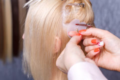 Hair extensions procedure. Hairdresser does hair extensions to young girl, blonde in a beauty salon. Selective focus. The hairdresser does hair extensions to a royalty free stock image