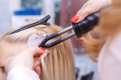 Hair extensions procedure. Hairdresser does hair extensions to young girl, blonde in a beauty salon. Selective focus. The hairdresser does hair extensions to a stock photo