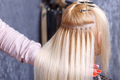 Hair extensions procedure. Hairdresser does hair extensions to young girl, blonde in a beauty salon. Selective focus. The hairdresser does hair extensions to a royalty free stock images