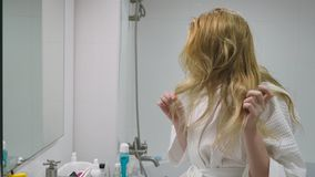 Hair health , hair loss concept. Woman combing her blond damaged dry hair in the bathroom. Hair health concept. Woman combing her blond damaged dry hair in the stock video