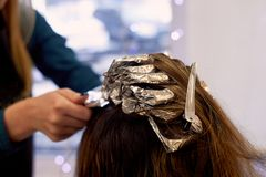 Hair highlighting with foil.Beauty shop.Hairdresser`s hands royalty free stock image