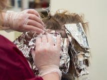 Hair highlights in the beauty salon. The foil on the hair while highlighting royalty free stock photo